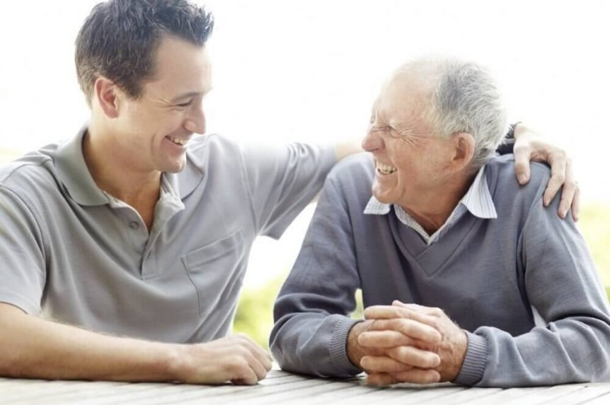 A middle-age man and an old man laughing to each other