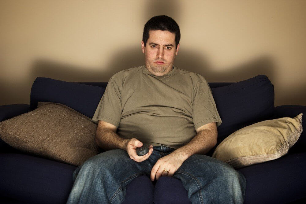 A man in a brown t-shirt sitting on a blue couch looks sad while holding a remote control
