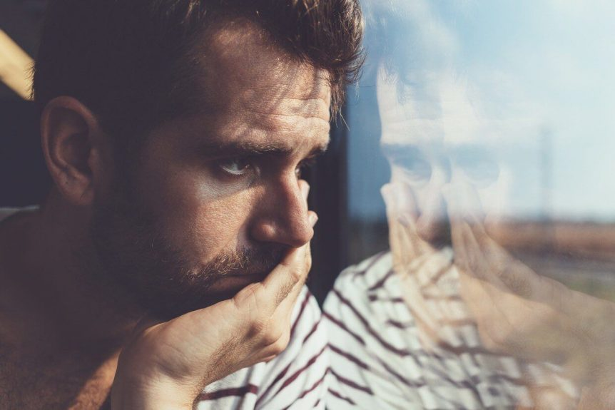A matured man wearing stripe shirt and staring at a transparent window