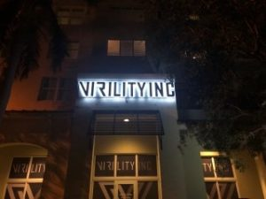 "Night time view in front of a medical clinic named ""Virility Inc""."