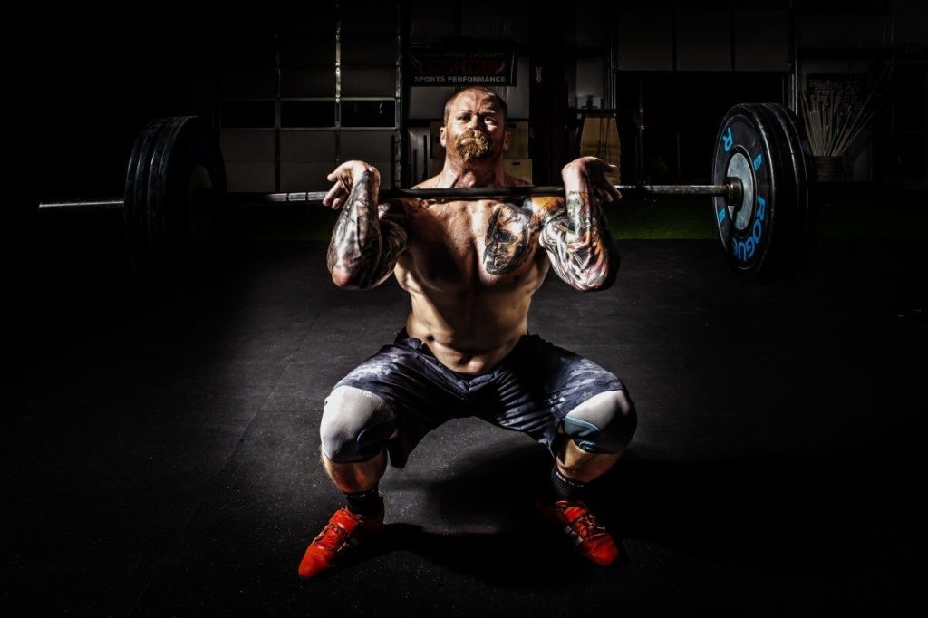 A man with tattoo on his body lifting a barbell