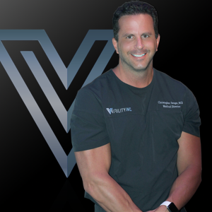 A man in a dark t-shirt smiling with a logo of Virility behind